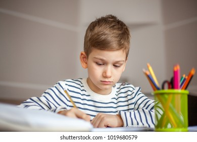 Young boy doing his homework at home, fron view