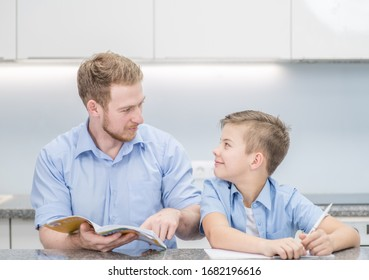 Young boy doing his school homework with his father