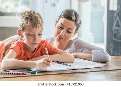 Young boy doing his school homework with his mother, at home, he is writing on a book