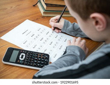 Young boy doing maths homework test times tables multiplication exam paper sat at table homeschooling education with calculator and books holding pencil learning mathematics  getting answers right