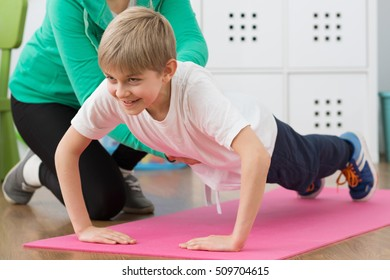 Young boy doing push-ups in physiotherapist's room