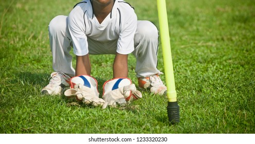 Young boy doing wicket keeping practice in a green field