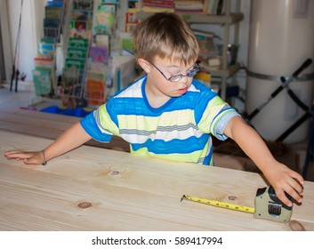 Young Boy With Downs Syndrome Playing With Measuring Tape