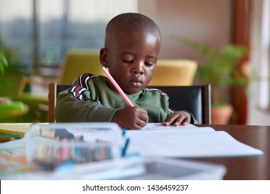Young boy drawing colouring in book, artistic creative