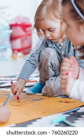 Young boy drawing on orange paper with his classmate in nursery school