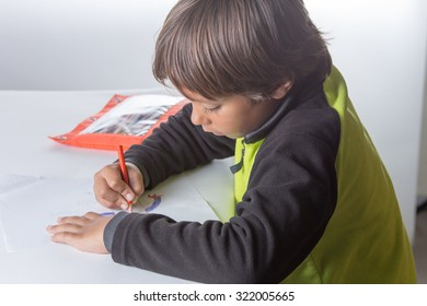 Young boy drawing picture for homeschool project.