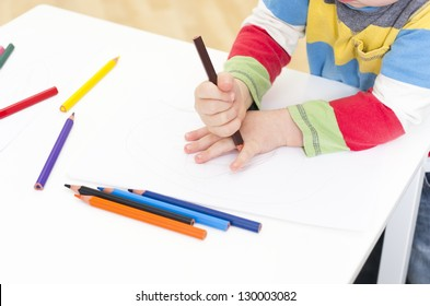 Young boy draws around his hand