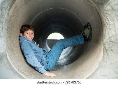 Young boy dressed in blue and gray playing in the slide - toboggan