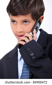 Young boy dressed in a business suit with a mobile phone