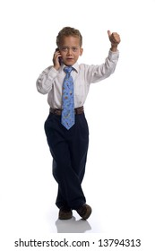Young boy dressed as businessman talks on the mobile phone - isolated on white