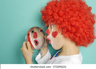 Young boy is dressed up as clown with red wig for carnival looking surprised in mirror