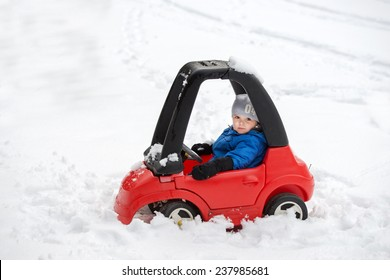 A young boy dressed for cold weather sits in a red toy car stuck in the snow during the winter season.