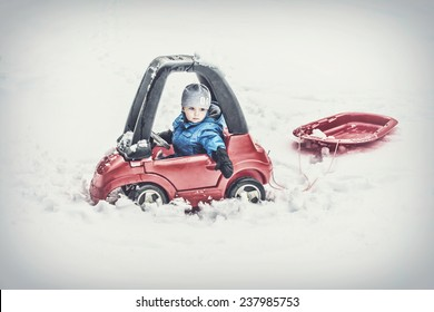 A young boy dressed for cold weather sits in a red toy car stuck in the snow pulling behind a red sled during the winter season.  Filtered for a retro, vintage look.