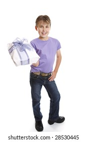 A young boy dressed in jeans and t-shirt holds a present tied up with a big ribbon ow.
