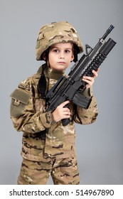 Young boy dressed like a soldier with rifle isolated on gray background