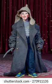 Young Boy Dressed in Over Sized Grey Coat and Floppy Hat Holding Prop Toy Sword with Face Painted in Clown Make Up, Standing on Stage Looking at Camera