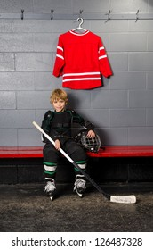 A Young Boy in Dressing Room partially dressed in hockey equipment
