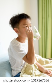 Young boy drink a water from a glass.