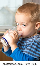 Young boy drinking milk out of glass in the kitchen