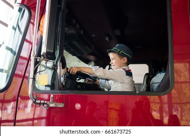 Young boy in driving seat of truck, holding steering wheel, smiling