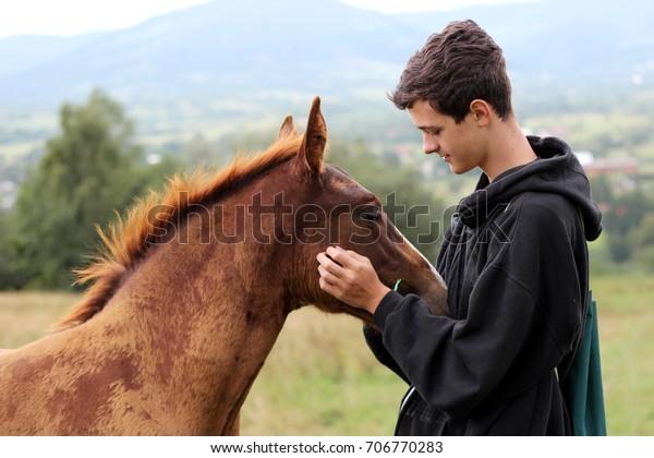 Joven que durante el alto montaje se encuentra con un caballo joven y se comunica con él, naturaleza salvaje, el concepto de amistad de personas y animales, estilo de vida verano exterior