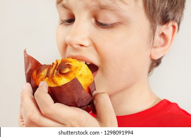 Young boy eat the appetizing muffin on a white background close up
