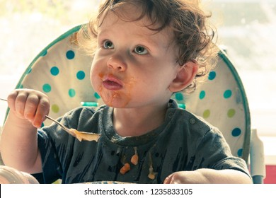 A young boy eating baked beans in a highchair