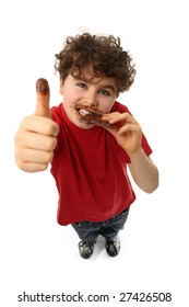 Young boy eating bar of chocolate, showing Ok sign  isolated on white background