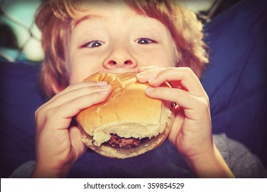 young boy eating a hamburger outdoors, vintage instagram effect.