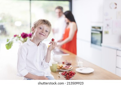 young boy eating  strawberries in family kitchen