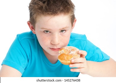 Young boy eating a sugary doughnut. Isolated on a white background.