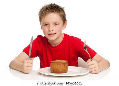 Young boy eating a tasty pork pie with a knife and fork. Isolated on a white background.