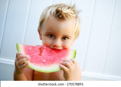 Young boy eating watermelon