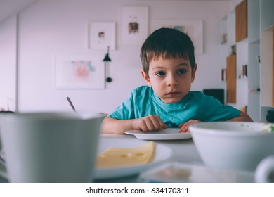young boy eating without paying any attention