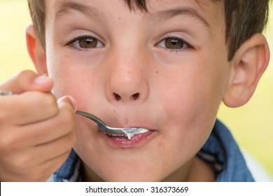 Young boy eating yoghurt.