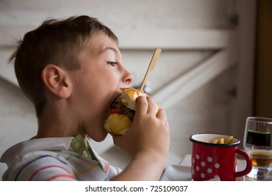 Young boy eats big hamburger