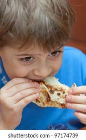 Young boy eats pancake with jam