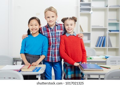 Young boy embracing two intercultural classmates in classroom
