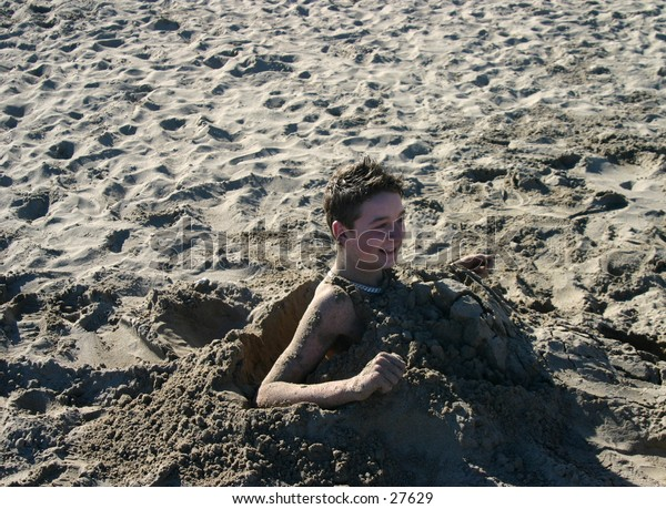 young boy emerging from being burried in the sand