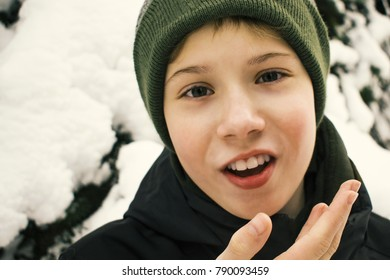 young boy emotionaly and indignantly speaks with a smile and gestures, dressed in a green hat and jacket,  winter background
