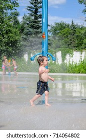 A young boy enjoying the sprinklers at the park.