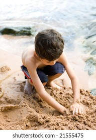Young boy enjoys playing with the sand by the beach