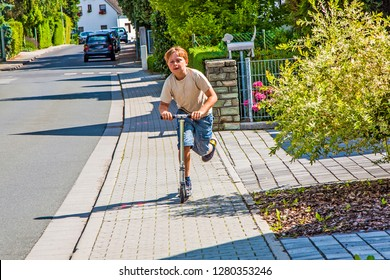 young boy enjoys skating with his pust scooter at the sidewalk