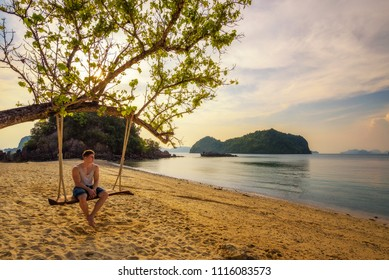 Young boy enjoys sunset sitting on a rope swing at a beautiful beach on Ko Hong island in Thailand