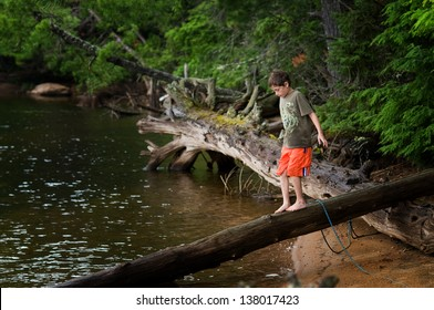 young boy exploring by a remote lake