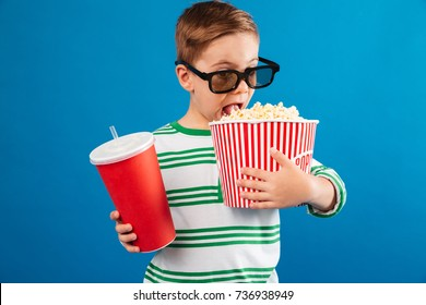 Young boy in eyeglasses preparing to watch the film while eating popcorn and holding cup of soda over blue background