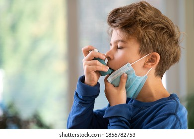 Young Boy with face mask using asthma inhaler to treat breathe issues and inflammatory disease amid Covid-19 pandemic. Difficulty Breathing in a Face Mask concept.