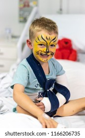 Young Boy with Face Painted in Hospital with a Broken Arm in Sling