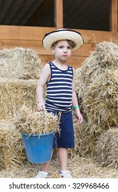 young boy farmer is holding a bucket of barley at the horse stall at the farm - focus on the right eye