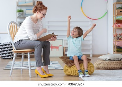 Young boy feeling happy because he made progress in speech lessons during meeting with speech therapist